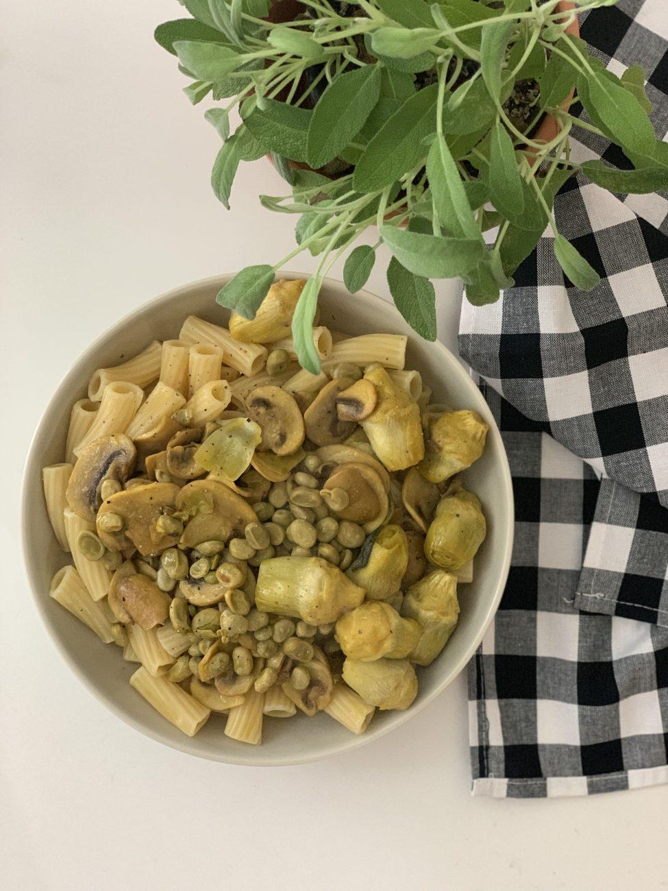 Pasta con salteado de champiñones y habitas baby con azafrán y piel de limón